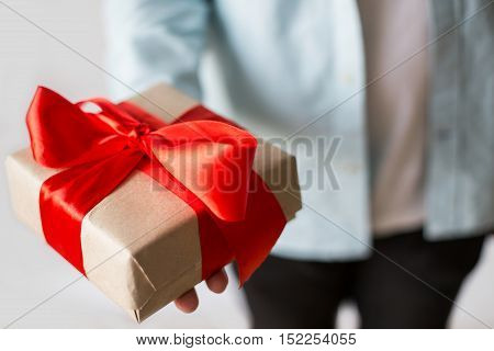Man giving present with craft paper box and red ribbon. Hand with gift