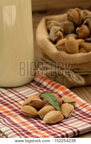 Almond milk with almonds on a wooden table and focus with shallow depth of field