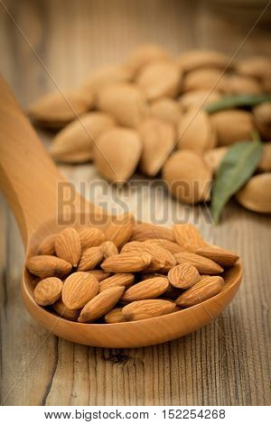 Almonds on brown wooden background with the focus in the foreground