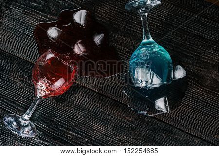 Wine glasses with colorful liquids and ice cubes lying on the dark wood surface. Flat lay