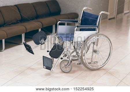 Empty wheelchair parked in hospital. Empty wheelchair