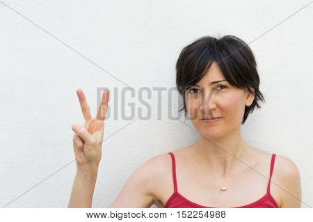 Young Woman Making Peace Sign in Front of a Wall