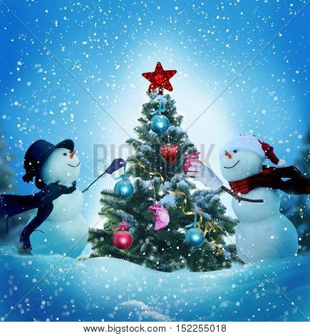 Snowmen decorating a christmas tree.Merry christmas and happy new year greeting card with copy-space.Happy snowmen standing in winter christmas landscape.Snow background