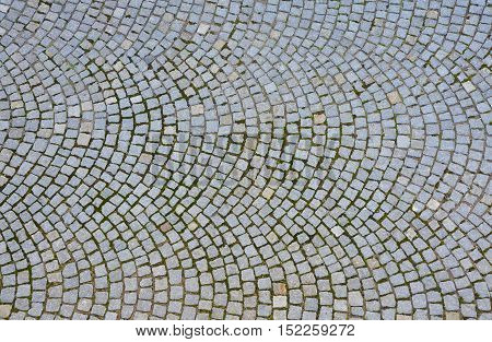 Paving stone surface. Old cobblestone road with circular pattern. Top view.