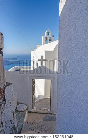 One of the typical narrow streets in Thira on the greek island Santorini in the southern Aegean Sea with its white buildings bell tower and a cross of Greek Orthodox Church.