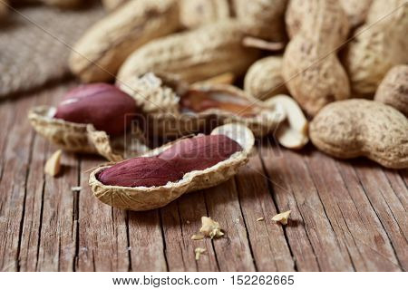 closeup of a pile of peanuts in its shells, on a rustic wooden surface