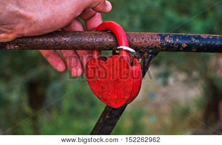 hand holding a red lock attached to the metal frame