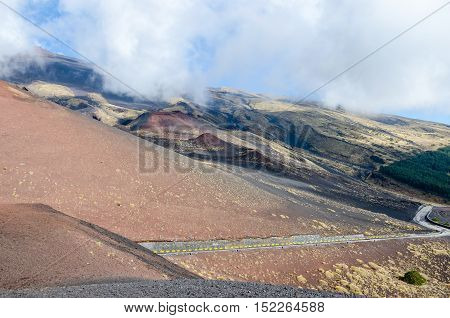 Southern flank of Mount Etna an active stratovolcano on the east coast of Sicily Italy showing lateral crater and the road leading from Sapienza Refuge ski area.