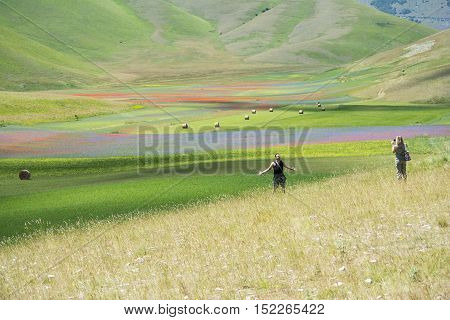 CASTELLUCCIO,ITALY-JULY 9,2016:Photographers stroll and take photograf of multicolored flower meadows on the plateau of Castelluccio during a summer day.
