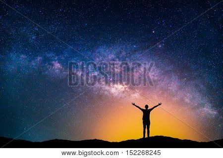 Landscape with Milky way galaxy. Night sky with stars and silhouette happy man on the mountain.