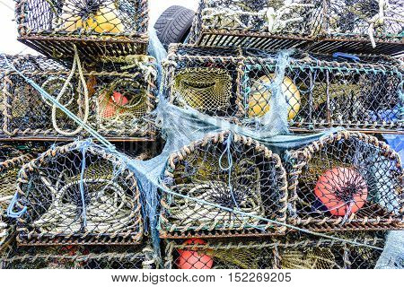 Textures and colors of stack of lobster pot creels on the Isle of Skye Scotland with tangled ropes and blue netting and colorful buoys