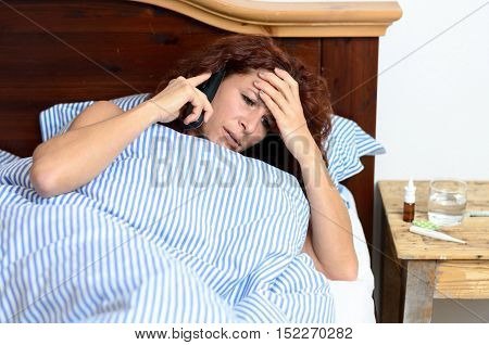 Woman On Phone With Medicine Beside Her In Bed