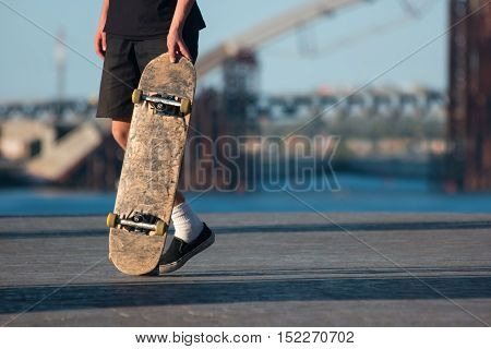 Guy with skateboard. Skater on blurred background. Be bold and risky. Sport that grew into culture.
