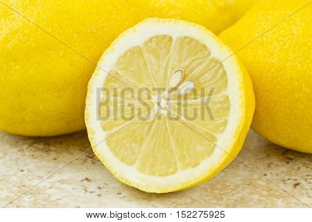 sliced lemon with pips isolated on a brown textured background