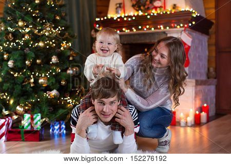 christmas x-mas family people happiness concept - happy parents playing with pretty baby boy
