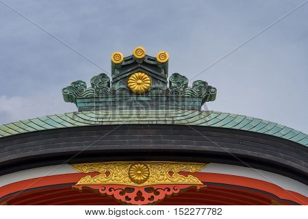 Kyoto Japan - September 17 2016: Fushimi Inari Taisha Shinto Shrine. The crest of a roof shines in bronze and gold against a blue sky above vermilion facial board.