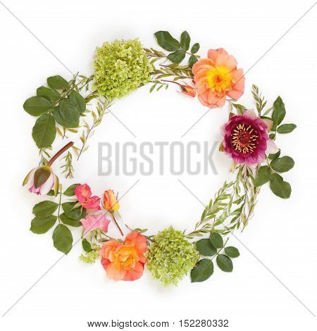 Floral round crown (wreath) with flowers and leaves. Flat lay top view. Creative arrangement with pink and orange roses gray grefsheim (spiraea cinerea) leaves sevenbark (hydrangea arborescens) and nymphaea waterlily.