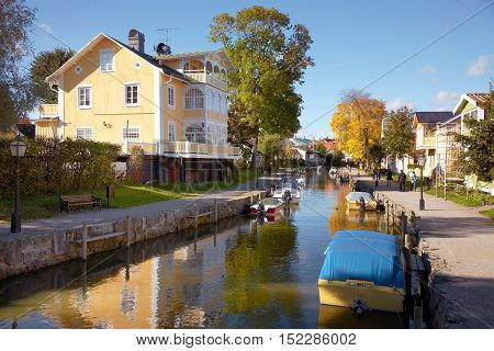 Trosa, Sweden - October 6, 2012: Moored boats in Trosa River in front of a yellow turn of the century building..