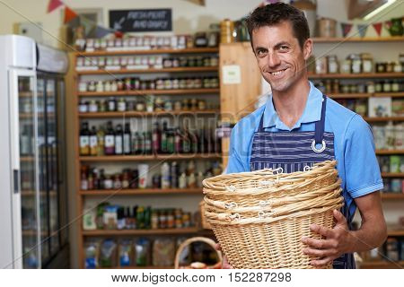 Portrait Of Man Working In Delicatessen Holding Baskets