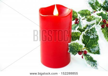 A medium sized red wax candle with an artificial holly branch decorated with glitter and glass stones as christmas decoration isolated on white background with copy space.
