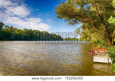 Tisza river in Hungary. The Tisza or Tisa is one of the main rivers of Central Europe. Cloudy blue sky, Rippling water. Tree branch over the river. Green forest. Summer season landscape.