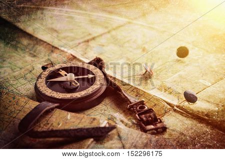 Old compass and mark on the map. Photos in a grunge style.