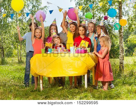Group of happy age-diverse kids standing next to the table with Birthday cake at the outdoor B-day party