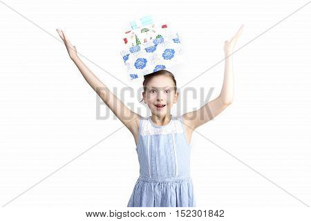 Birthday, holidays, Christmas, Presents, Childhood, people concept - the portrait of surprised little girl holding present boxes on her head isolated over white