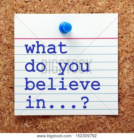 The question What Do You Believe In? in blue text on a note card pinned to a cork notice board as a reminder of your values and belief system