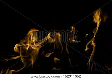 Snapshot of yellow, flickering tongues of fire dancing and twisting on black background