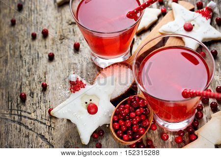 Cranberry juice or drink and funny cookies shape santa healthy Christmas treats for kids on wooden background