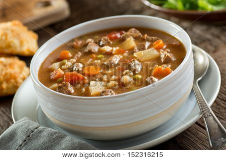 A bowl of delicious beef and barley soup with carrots tomato potato celery and peas.