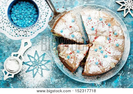 Festive Christmas winter cake with powdered sugar and snowflake sprinkling on blue background with decorations Christmas dessert recipe