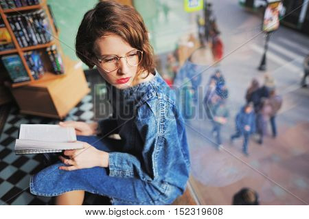 girl in the library or the bookstore looking out the window with a book in his hand