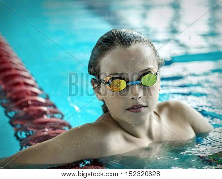 Swimmer child. Portrait of swimming child athlete with goggles after training in waterpool.