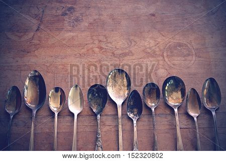 Over head flat lay view of a collection of silver tarnished spoons side by side against a rustic wooden table