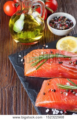 Raw salmon fillet and ingredients for cooking on a slade board and brown wooden background.
