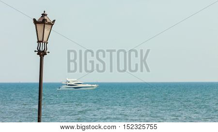 Black retro old styled lantern lamp on sea ocean water background. Yacht ship seiling. Horizontal photo.