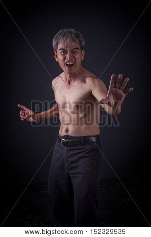 asian man actiing chinese kungfu fighting low key lighting photography