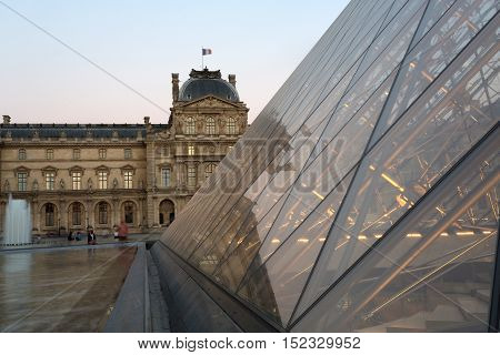 PARIS - AUGUST 15 2016 Louvre museum at twilight in summer. Louvre Museum is one of the world's largest museums every year museum visits are more than 8 million visitors.