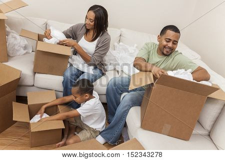 African American family, parents and son, adults and child, unpacking boxes and moving into a new home.