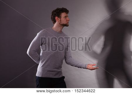 Dance and party. Young casual man asking elegant female dancer for dancing. Handsome male with shadow of woman.