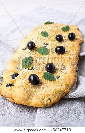Italian bread focaccia with olive garlic and mint vertical. Homemade traditional Italian bread focaccia on the linen napkin.