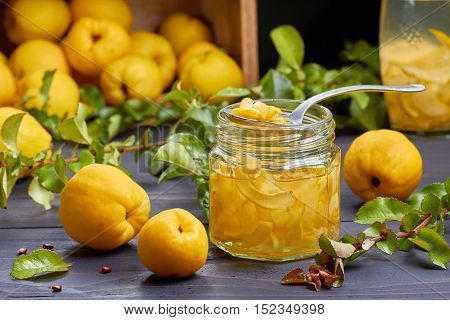 Syrup of japanese quince on fresh fruits background over dark wooden table.