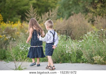 siblings sitting on a sidewalk and kissing