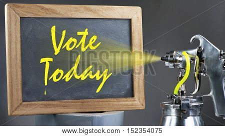 Spray painting vote today on a blackboard.
