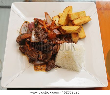 Traditional Peruvian dish Lomo Saltado (Beef saltado). Lomo saltado is a stir fry that typically combines marinated strips of sirloin with onions, tomatoes, french fries and typically served with rice