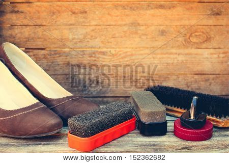 Women's shoes and care products for footwear on wooden background. Toned image