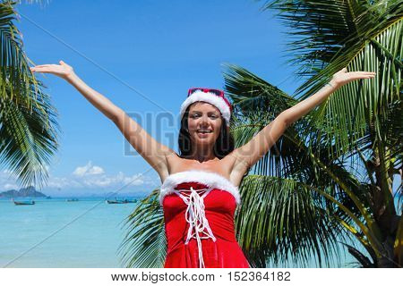 Beautiful woman in Mrs. Claus custume on tropical beach with palms, Christmas vacations concept