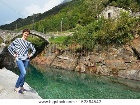Happy woman on the clear Verzasca river background. Travel concept